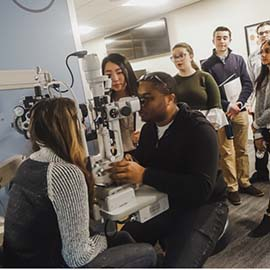 Students using optometry equipment during OLE program in 2019.