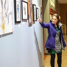 Artist pointing to artwork