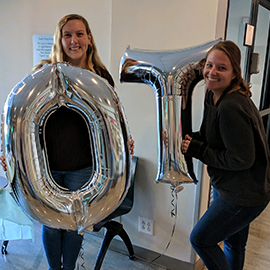"Two OT students holding ""O"" and ""T"" balloons"
